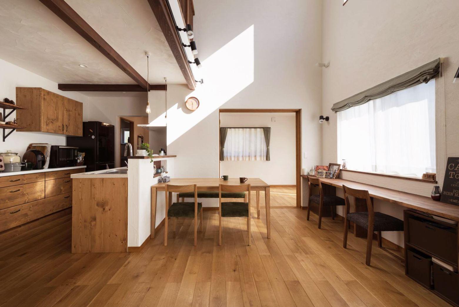 アイジースタイルハウス【収納力、自然素材、間取り】吹抜けのダイニングキッチン。無垢フローリングの色、質感に合わせてキッチンとカップボードをコーディネートした。『アイジー』の家は断熱性がとても良いので、吹抜けにした方が冷暖房効率がより高まる
