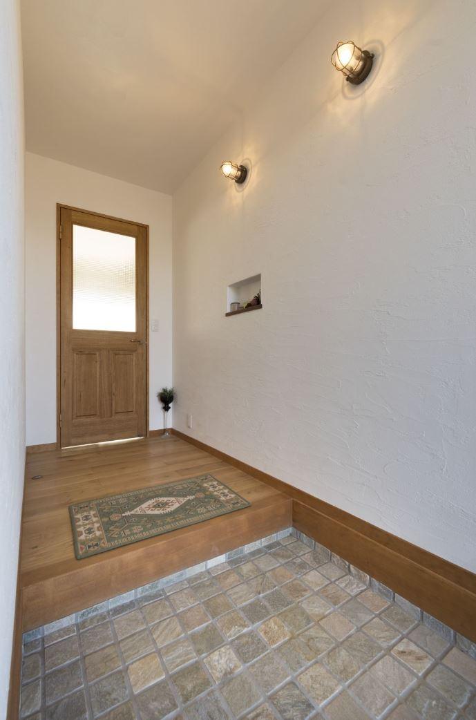 アイジースタイルハウス【収納力、自然素材、間取り】シンプルにまとめた玄関ホール。調湿、消臭効果にすぐれた漆喰の効果で、不快な臭いが一切しない。タイルの三和土とマリンランプがアクセントに
