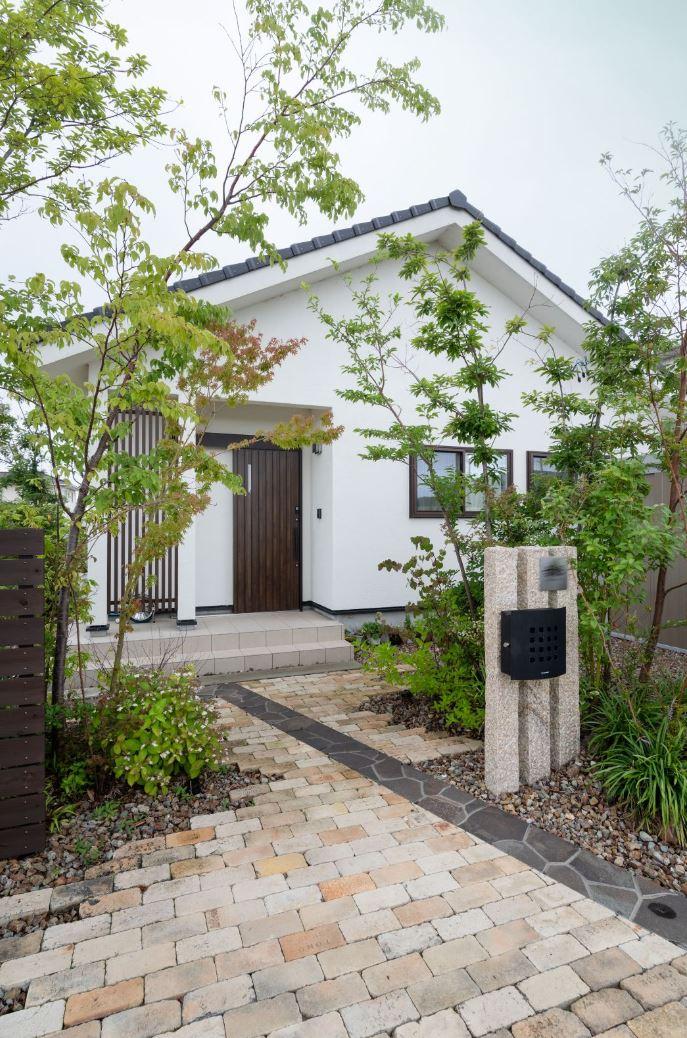 アイジースタイルハウス【子育て、自然素材、平屋】家族の新しい物語が始まる平屋。外壁の遮熱漆喰は、無塗装で汚れにくいのでメンテナンス負担が少なく、太陽熱を反射するので室内の温度を快適に整えてくれる。植栽まで含めたエクステリアも『アイジー』の設計施工で、建物とのバランスも考慮されている