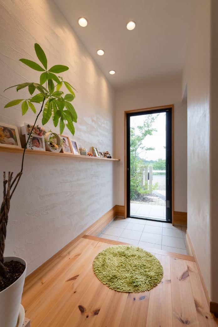 アイジースタイルハウス【子育て、自然素材、平屋】入った瞬間、天然木のならではのやさしい香りに包まれる玄関ホール。漆喰の壁に棚を造作してホームギャラリーに。収納スペースも充実