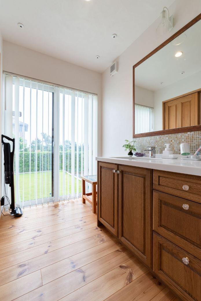 アイジースタイルハウス【子育て、自然素材、平屋】庭の景色を見ながら洗顔できるサニタリー。木枠のワイドな鏡にモザイクタイルを組み合わせたお気に入りの洗面台は、前に立つたびにテンションが上がる
