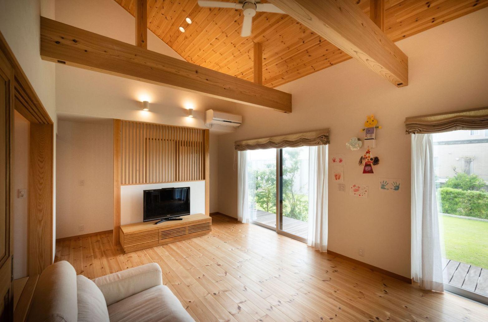 アイジースタイルハウス【子育て、自然素材、平屋】大きな開口部から庭を眺めながら過ごせるリビング。天井の羽目板と南北に走る太い梁が安心感を与える。テレビ背面の格子がアクセントに