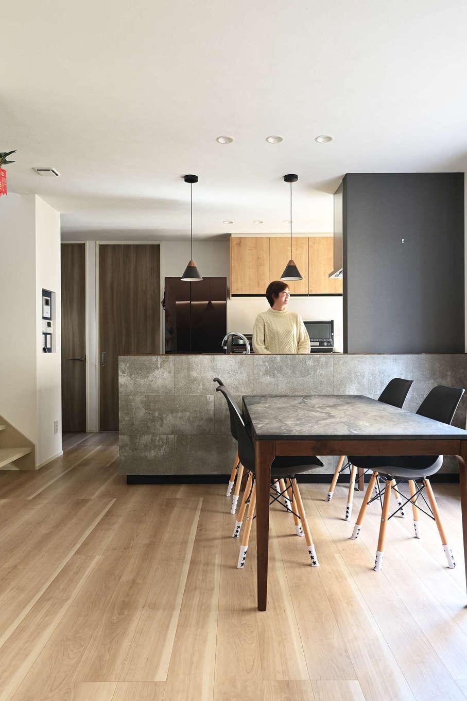 トーリンホーム【デザイン住宅、子育て、間取り】リビングのアクセントクロスと同様に、対面キッチンの腰壁にも家具調に「ソリド」を張って統一感を演出。ダークグレーのクロスやペンダント照明とも絶妙にマッチして、スタイリッシュな空間に仕上がった。ダイニングテーブルもデザインテイストを揃えた