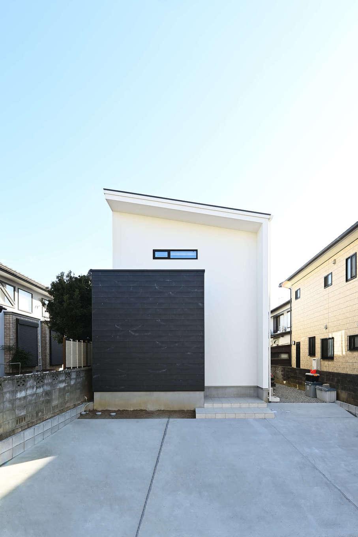 トーリンホーム【デザイン住宅、子育て、間取り】片流れの屋根と白×黒のコンビネーションがクールな外観。道路側からの視線を遮るために玄関ポーチを黒い塀で隠している。黒い塀はコンクリート系の新素材「ソリド」を採用。自然のムラによる個性的な風合いとざらりとした素材感が外観の意匠性を高めている