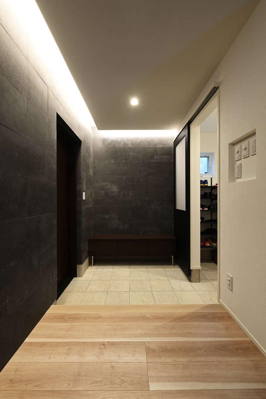 トーリンホーム【デザイン住宅、子育て、間取り】玄関からリビングに至る壁にも「ソリド」を採用し、内と外の一体感を強調。間接照明を用い、ホテルライクで洗練された雰囲気を演出。シューズクロークから手洗い場を抜けてキッチンに至る動線も確保されている