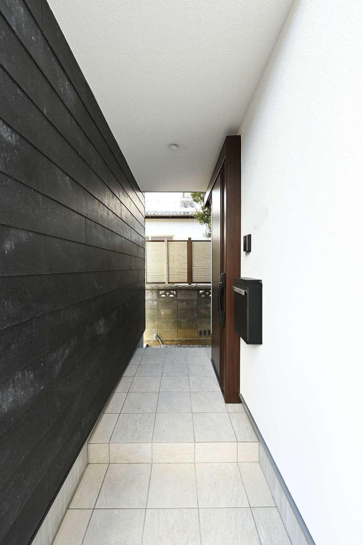 トーリンホーム【デザイン住宅、子育て、間取り】黒い塀の裏面の壁面も表面と同素材で統一。ポーチの奥行き感がいっそう強調され、壁の風合いが上質で洗練された雰囲気を醸し出している