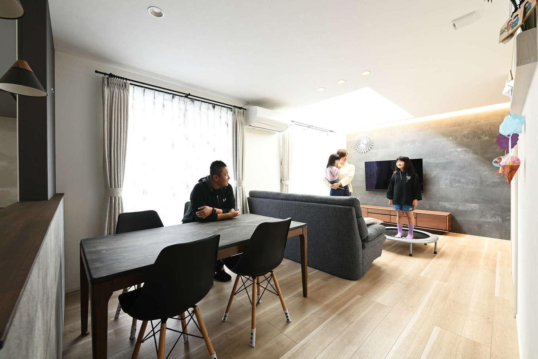 トーリンホーム【デザイン住宅、子育て、間取り】リビングの吹き抜けから光が注ぐLDK。玄関とつながる「ソリド」のアクセントウォールが室内をスタイリッシュモダンに演出