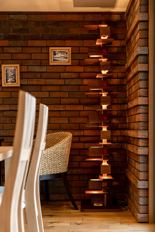 住宅工房 アリアンス【富士市伝法2001-35・モデルハウス】ライトの名作であるフロアーランプの「タリアセン 2」。幾つものチェリー材のブロックで構成され、それぞれに白熱電球が組み込まれている。計算されたデザインにより、木目と木漏れ日の光が美しく調和し、暖かくムーディーな空間を演出する