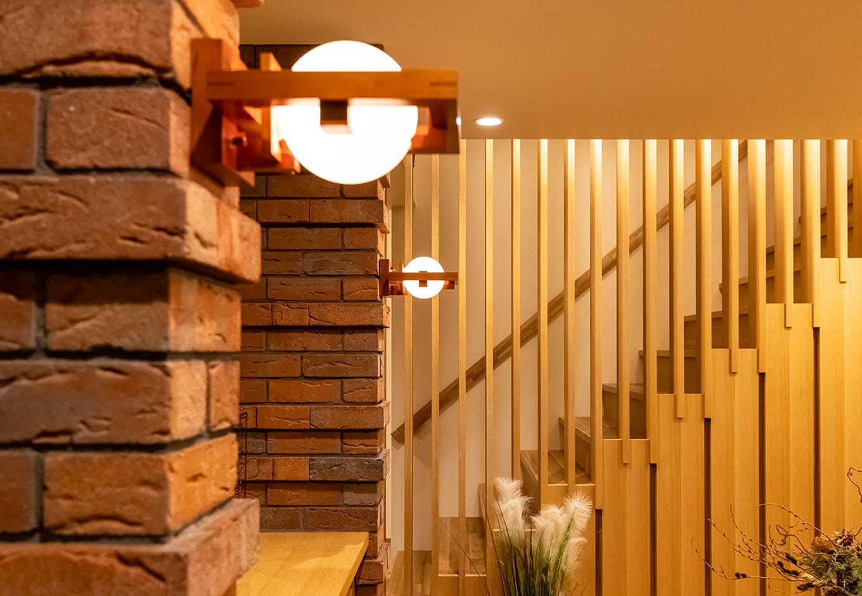 住宅工房 アリアンス【富士市伝法2001-35・モデルハウス】木とガラスで構成されたブラケットライト「ロビー 1」がレンガをやさしく照らす。ライトの初期の建築様式であるプレイリースタイル(草原様式)を代表する住宅、フレデリック・ロビー邸のリビングルームのためにデザインされた照明器具
