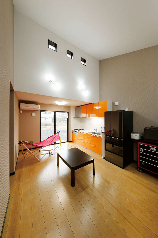住宅情報館【デザイン住宅、平屋、ガレージ】LDKは勾配天井を利用した吹き抜けを設計し、縦の広がりが開放感を生む。天井付近に並ぶ四角い窓から、柔らかな光が注ぐ