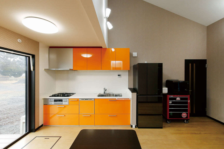 住宅情報館【デザイン住宅、平屋、ガレージ】鮮やかなオレンジ色の壁づけキッチンを選び、LDKの広さを確保した。「キッチンや浴槽などの設備類は標準仕様のグレードが高く、浴室はTV付き。それも魅力でしたね」そう夫婦は話す