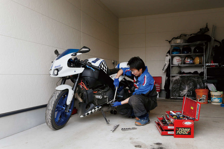 住宅情報館【デザイン住宅、平屋、ガレージ】この日はアメリカ製バイクの手入れ中。車やバイクの工具類が一通り揃っているため、仲間たちが「工具を貸して」と立ち寄ることも多い。ガレージ内から玄関に続くドアがあり、生活動線も便利だ