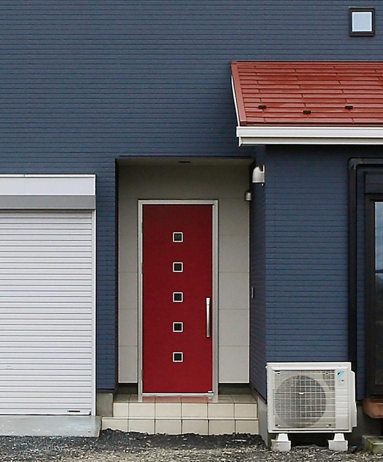 住宅情報館【デザイン住宅、平屋、ガレージ】「濃いブルーの外壁をオーダーしたところ、玄関ドアを赤に、その周りを白く囲むデザインを提案してもらいました。想像以上にかっこよく仕上がり、お気に入りです」とTさん。