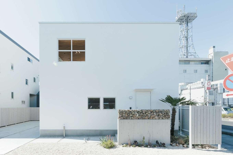 住家 ~JYU-KA~【静岡市清水区七ツ新屋357-2・モデルハウス】キューブ型のファサードは周囲に洗練された雰囲気を放つが、近づくと塗り壁ならではのやさしい風合いが目に届く。外界とつながるのは2階の十字窓とバルコニーの上に大きく開いた空。立地に左右されることなく、人目を気にせず自分たちらしい日常を送ることができる。植物の取り入れ方も含め、外構も参考になりそうだ