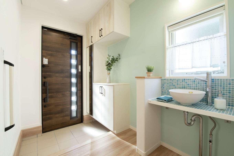 遠鉄ホーム【浜松市中区和合町・モデルハウス】玄関ドアを開けると、ブルーのモザイクタイルが貼られた手洗いコーナーが目に入る。帰宅後すぐ手洗いとうがいができ、その先に続くファミリークローゼット、浴室へリビングを通らず一直線に移動できる間取りが秀逸だ