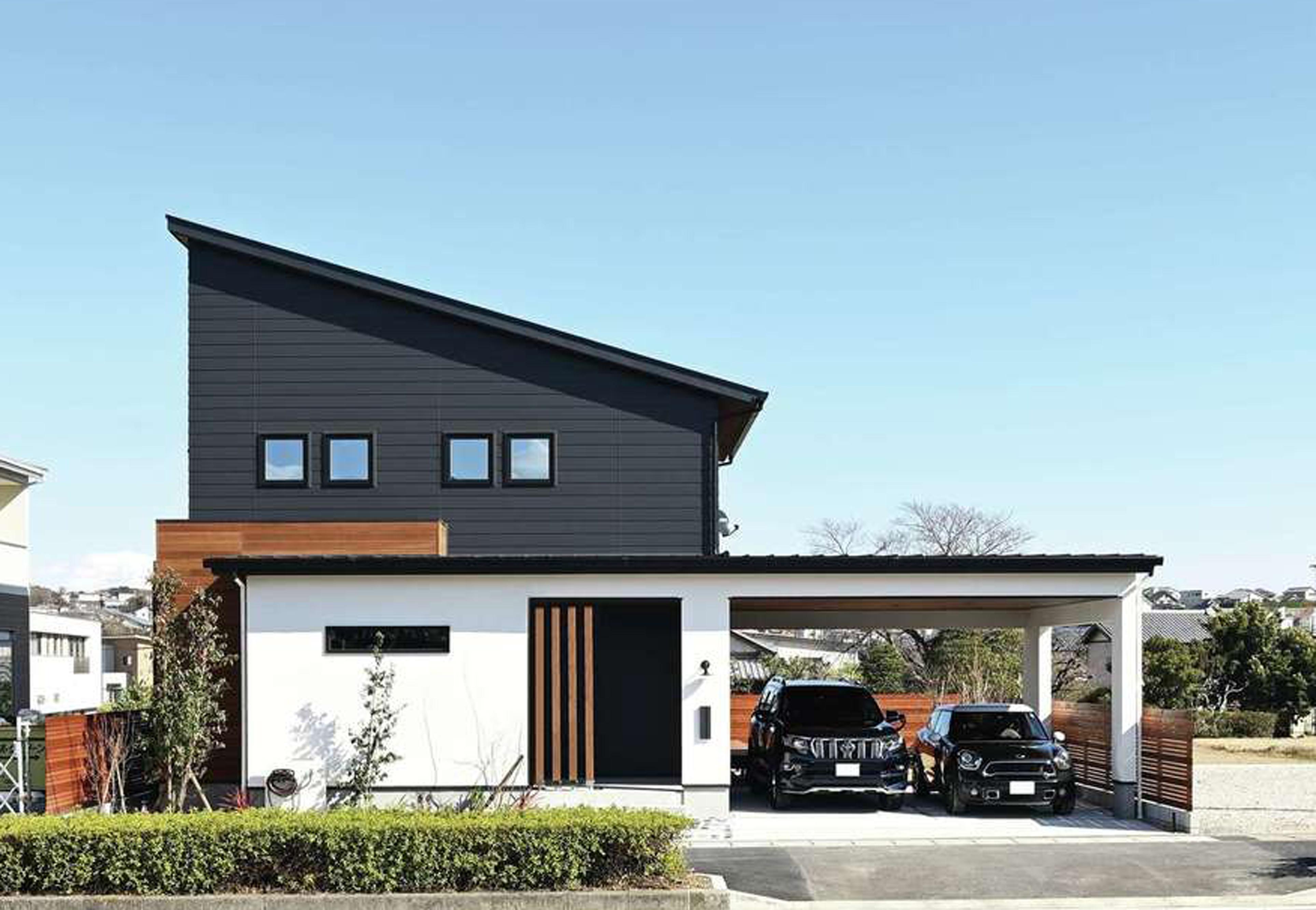 Yamaguchi Design 【磐田市見付1853-19・モデルハウス】建物の1階とガレージの屋根が一体化したスタイリッシュな外観デザイン。水平、垂直の美しいラインも計算されている。黒いガルバリウム、白い塗り壁、天然木の異素材がバランス良く調和し、青空にもよく映える。片流れの屋根に7kWの太陽光発電を搭載