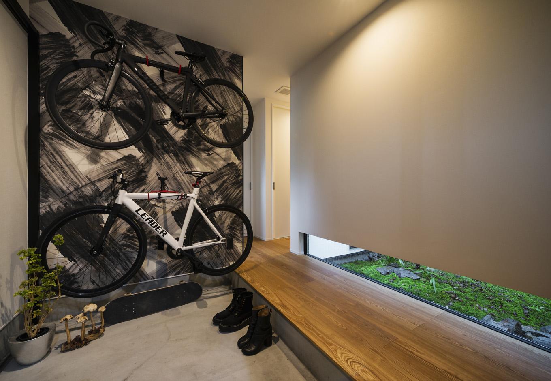 S.CONNECT(エスコネクト)【趣味、夫婦で暮らす、平屋】自転車を壁掛けにした玄関。地窓の緑が白黒の空間に映える