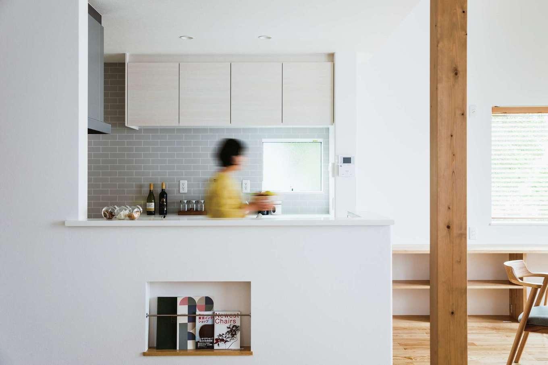ワンズホーム【デザイン住宅、子育て、建築家】奥さまの好みをもとに、ナチュラルな木の色を活かす内装に。キッチン壁にはタイル調クロスを配置