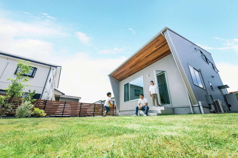 ワンズホーム【デザイン住宅、子育て、建築家】袖壁を斜めに出し、軒を広げて片流れの外観フォルムをユニークにアレンジ。LDKに設置したドアから、庭へ自由に出入りできるため、芝生の上もリビングの一部のよう