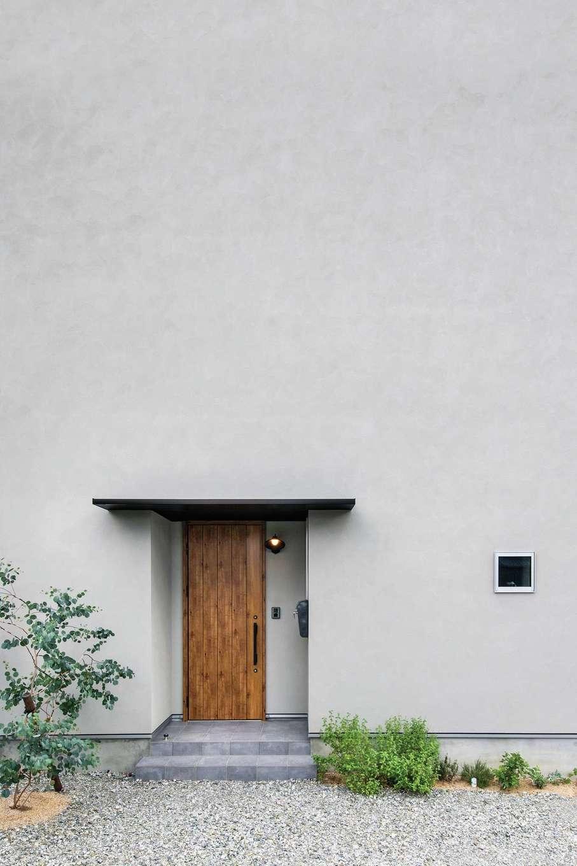 ワンズホーム【デザイン住宅、子育て、建築家】家の北側は、窓のない潔いデザインが目を引く。木製ドアと塗り壁の相性もいい