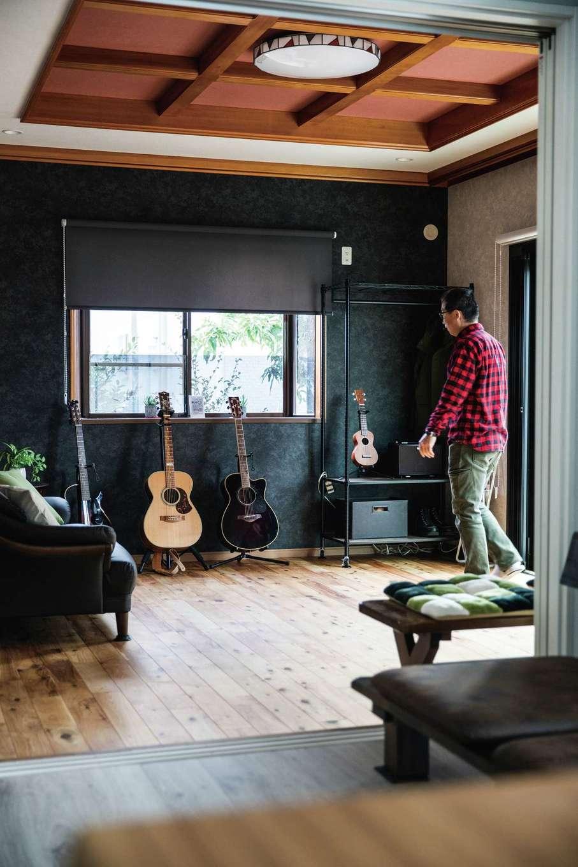 ほっと住まいる|無垢の床、シックな壁紙、そして古い家の天井が織りなすモダンなデザインが目を引く。大好きな曲を、ゆっくりとギターで奏でる時間を楽しんでいる