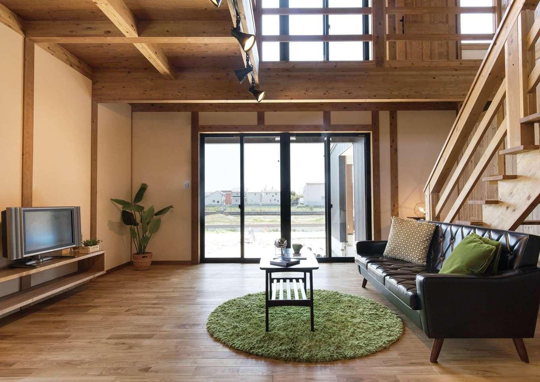 サイエンスホーム【1000万円台、デザイン住宅、省エネ】吹抜けの開放感が気持ちいい大空間リビング。窓を開けるとウッドデッキとつながり、外と内との一体感が生まれる。これだけ大きな吹抜けがあっても、標準仕様の外張り断熱によって上下階の温度差がほとんどなく快適に過ごせる