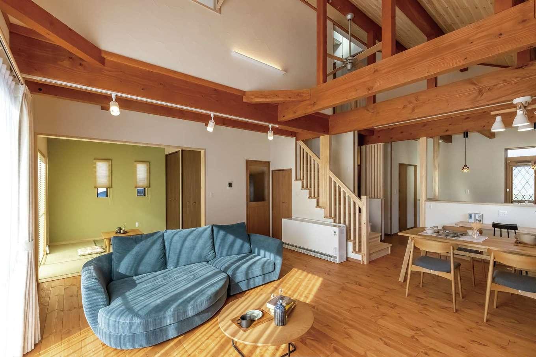 住まいるコーポレーション【デザイン住宅、自然素材、省エネ】14畳の勾配天井があるリビングダイニングは、開放感たっぷりのリラクゼーション空間。パインの床と梁を自然塗料で着色し、落ち着きがあって個性的な空間が実現