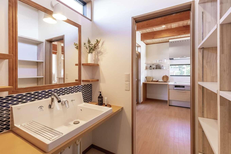 住まいるコーポレーション【デザイン住宅、自然素材、省エネ】手作りの洗面台に加え、収納棚をたっぷり設けた洗面スペース。洗面台には美容室仕様の鏡を使用。三面鏡の代わりに鏡の両側に棚を設け、タイル選びにもこだわった