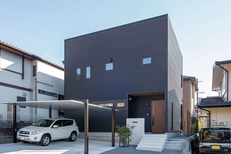 三和建設【デザイン住宅、子育て、間取り】黒ガルバリウムに玄関部分の軒天とドアの木目が映える。シンボルツリーは常緑樹のシマトネリコ