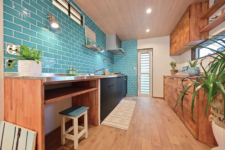 クローバーハウス 【デザイン住宅、省エネ、インテリア】ターコイズブルーのタイルとキッチンのステンレスがベストマッチ。子どもたちと一緒にお菓子づくりを楽しむためにワークトップを造作で延長した