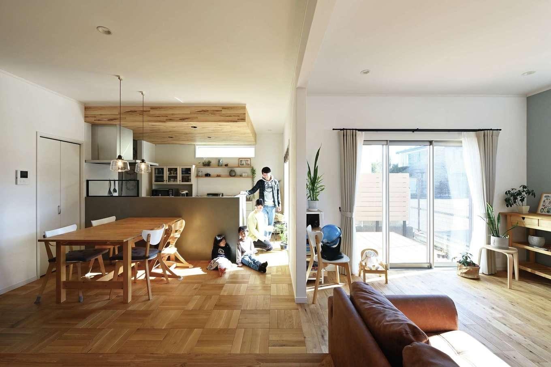 ハートホーム【子育て、自然素材、インテリア】キッチンの前面は、奥さまが好きな素材のモルタルで造作。レンジフードのアイアンフレームは特注で対応。木調の下がり天井もナチュラル感をプラスしている。オープンシェルフには、奥さまが大切にしている雑貨が並ぶ
