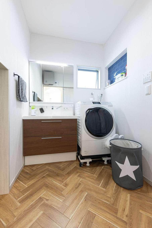 東海ハウス【子育て、間取り、スキップフロア】洗面脱衣室はヘリンボーン調のフロアであたたかな印象。左手には階段下のスペースを活かした収納が設けられている。洗剤などを置くためのニッチにはブルーのタイルを貼ってもらった
