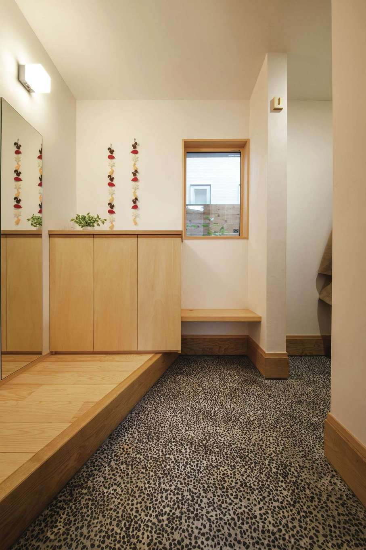 ぴたはうす 安食建設【デザイン住宅、和風、省エネ】洗い出しの土間が木の空間とマッチした玄関。土間収納もたっぷり設けてある。正面のベンチに子どもを座らせて靴を履かせたり、来客時にちょっと腰掛けたりするのに便利