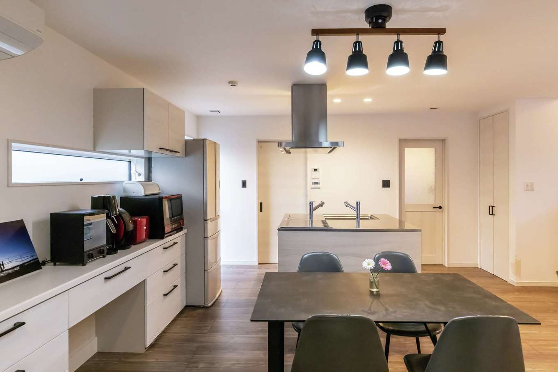未来創建【デザイン住宅、収納力、省エネ】アイランドキッチンを中心とした回遊しやすい間取りが、共働き夫婦の家事時間を短縮する。キッチンの色、質感に合わせて床と建具をセレクトした