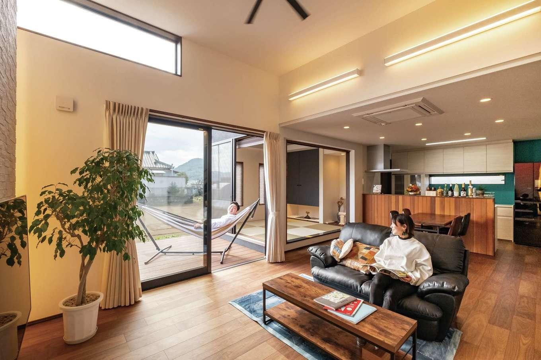 藤井建築事務所 -delphi-【デザイン住宅、間取り、建築家】天井が上がっており、階段上部の吹き抜けとあわせて高さを感じるLDK。キッチンの壁紙は奥様のチョイス