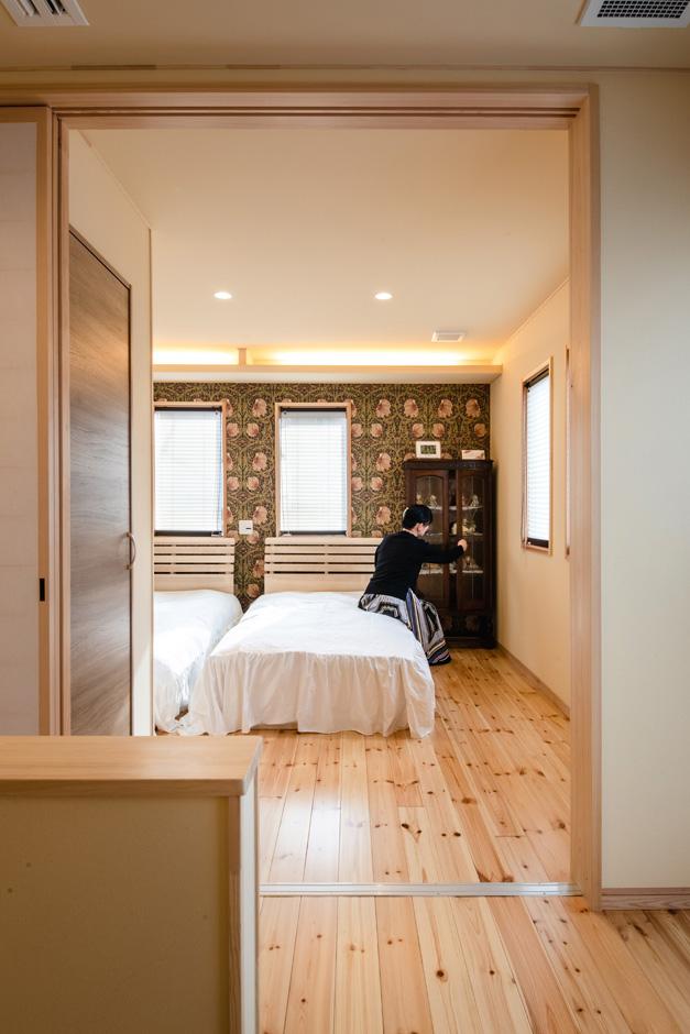 瀧口建設|2階の主寝室。ウィリアムモリスのアクセントウォールに英国製のアンティーク家具とドールが調和したモダンな雰囲気に。和の素材と洋のデザインが共鳴し、やわらかな間接照明が快適な睡眠を促す
