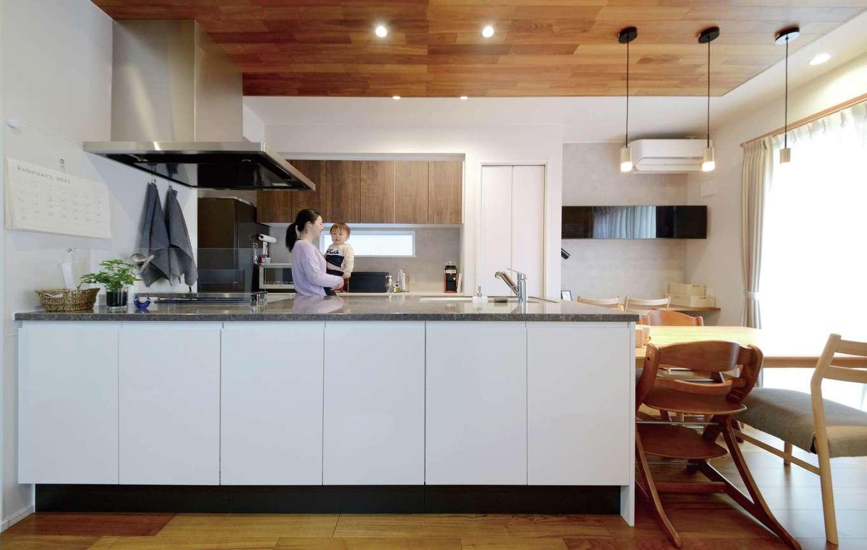 静鉄ホームズ【デザイン住宅、収納力、間取り】キッチンの天板は天然石を切り出したような気品ある表情が魅力の高級人造石を選択。下部は収納でLDKのスッキリに貢献する。右奥のブラックの収納はコーディネーターの提案。空間を引き締めるアクセントとして利いている