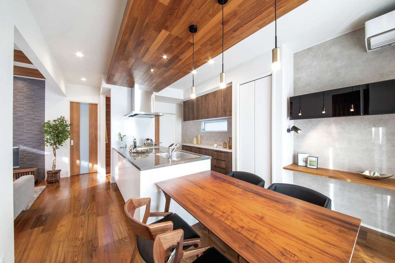 静鉄ホームズ【デザイン住宅、収納力、間取り】モダンさと木のぬくもりが心地よさを生むDK。2.7mの天井高から一段下げることで、落ち着きももたらされている。清水展示場を参考にした横並びのレイアウトが配膳と片づけの手間を軽減。右手の造作カウンターは事務作業や宿題用に