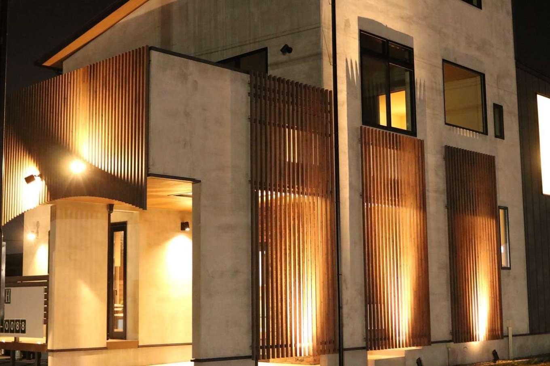 BE WITH 戸﨑建設【焼津市石津726付近・モデルハウス】ライトアップされたモルタル仕上げの外観は、道行く人の視線を集めている。カーブを描く縦格子もユニークだ