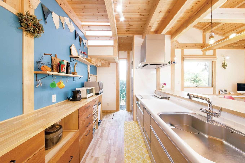住まい工房 整建【子育て、自然素材、間取り】使い勝手のいいキッチン。青い壁は奥さまがペイントし、カフェのようなおしゃれなキッチンに。階段下を活用したパントリー、階段の蹴込み板をアクリルにして光を取り込むアイデアも