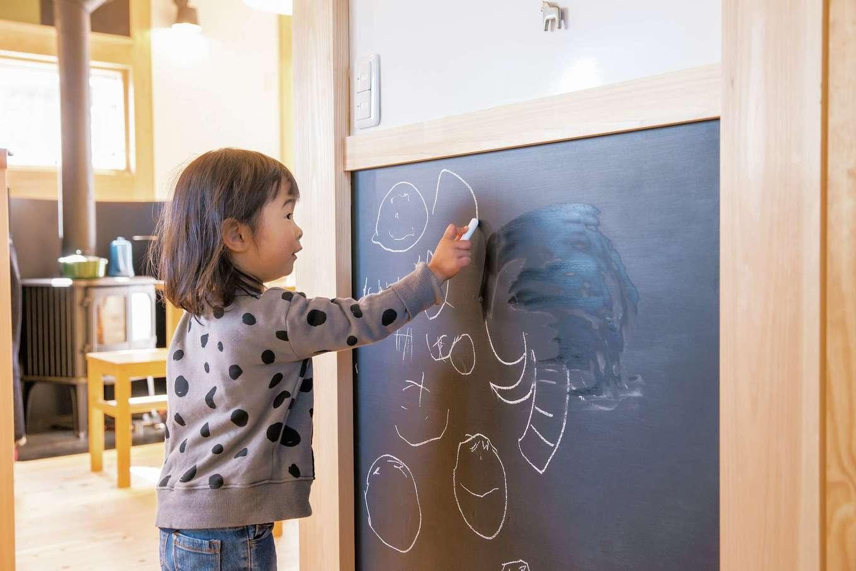 住まい工房 整建【子育て、自然素材、省エネ】キッチンそばの壁を黒板塗料でペイント。家事中も声かけができるので、さみしい思いをさせることもない。LDKの奥にあって目立たないから思う存分お絵かきでき、お子さんも大満足
