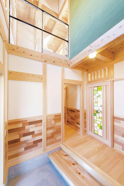 住まい工房 整建【子育て、自然素材、省エネ】緑の粉を混ぜ、櫛引して仕上げた土壁が吹抜けに映える開放的な玄関ホール。松や杉、ヒバなど、7 種類の木を組み合わせた腰壁は、大工さんと一緒にDIY