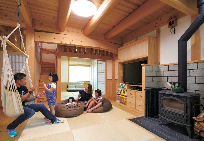 住まい工房 整建【子育て、和風、自然素材】無垢の木と自然素材に包まれた 畳敷きのリビングは約24畳。 3mもの天井高で開放感抜群。 収納たっぷりのTVボードは大工の造作。薪ストーブの前に家族 が自然と集まってくる