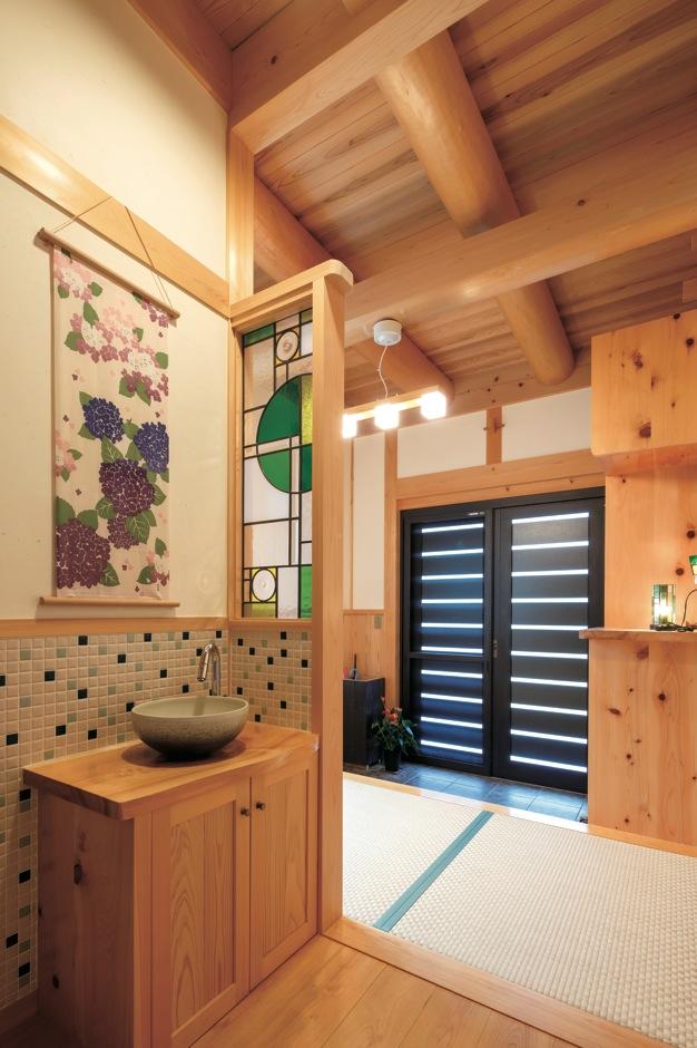 住まい工房 整建【子育て、和風、自然素材】外から帰ってきたらすぐ手を洗う習慣が自然に身につくよう、洗面台を玄関に設置。美しいステンドグラスが和の空間のアクセントに
