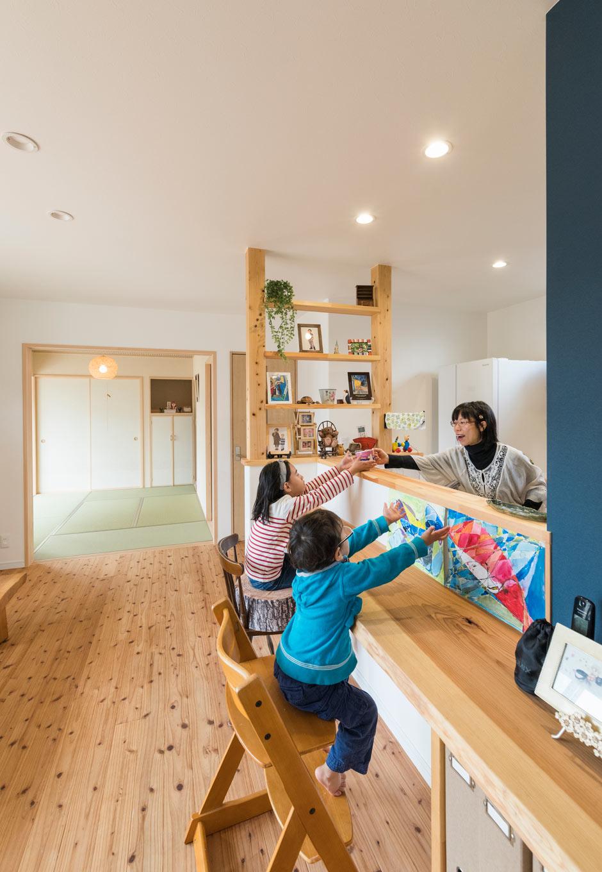 誠一建設 【子育て、収納力、間取り】対面キッチンは手元が見えないよう腰壁を高めに設定。奥の壁は圧迫感がでないように柱を活かして飾り棚に。和室で遊ぶ子どもたちの様子も見えやすい。続き間を開放すると広々感が味わえる