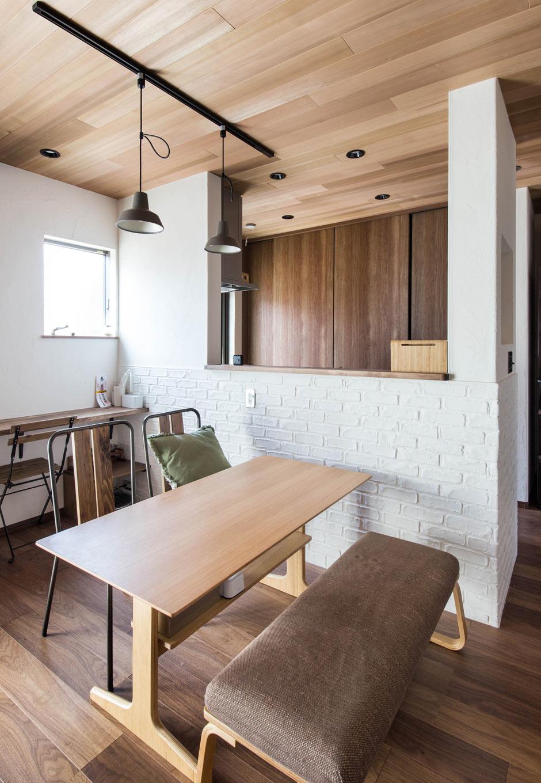 誠一建設 【収納力、ペット、インテリア】キッチンウォールは漆喰に型押しで表現したレンガ風のデザイン。リビングとトーンを合わせたマットカラーの扉を開けば大きなキッチン収納があり、生活を感じさせずに機能的。広々としたテーブルとベンチチェア、ヴィンテージ風ランプを飾り家具でカフェ風に