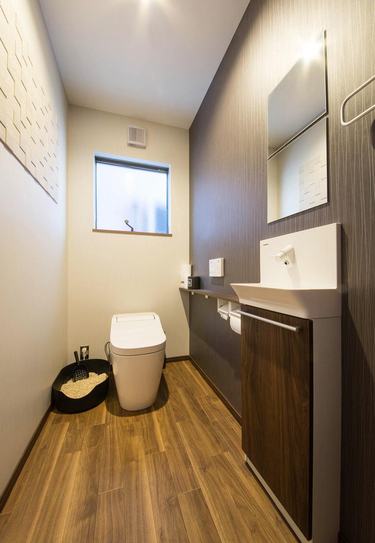 誠一建設 【収納力、ペット、インテリア】人と同空間に猫用トイレを設置し、流せる猫砂を使えばお手入れも楽々。使い勝手の良さを実現したシックなトイレ空間には、エコカラットの壁を配し、湿気を吸収して消臭効果も。猫用扉もあるため、猫も気兼ねなく自由に出入りできる