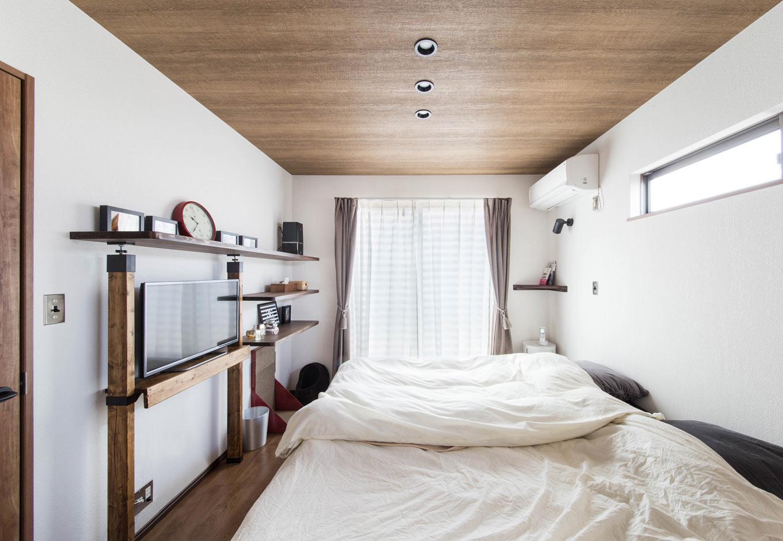 誠一建設 【収納力、ペット、インテリア】隣家と接する壁面の窓を上部に設置し、互いの家からの視界をずらしたベッドルーム。テレビラックや飾り棚など、過ごしやすさを考えて作られた、大工さんの手仕事が随所に施されている。家具の必要がなく、シンプルに過ごせる