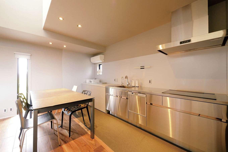 MABUCHI【デザイン住宅、建築家、ガレージ】無機質なトーンの空間に映えるオールステンレスのキッチン。熱に強いセラミック製のダイニングテーブルとともに設計前に決め、それに合わせて床やクロスの色を選んだので室内全体に統一感がある