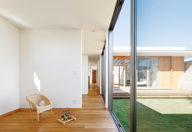 MABUCHI【デザイン住宅、建築家、平屋】ガレージから突きあたりの寝室まで直線に見通せる西側の廊下。右手に中庭、左手は子ども部屋2つ、ダイニングキッチン、バスルームが並ぶ